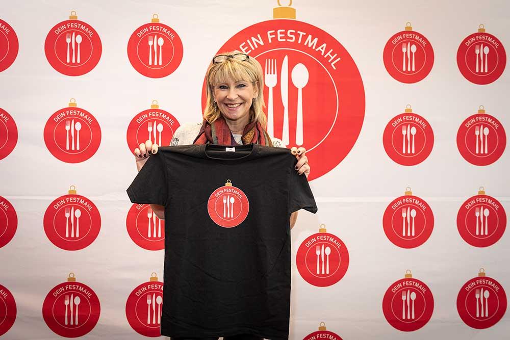 Claudia Jung präsentiert das Festmahl-Shirt